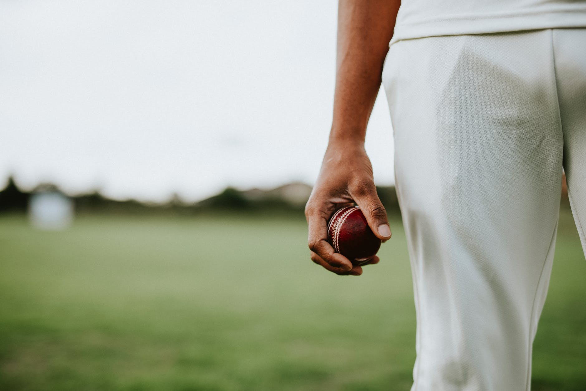 Sense of Belonging man holding cricket ball on a green field Post Image - 7 Personality Traits the Best Cricket Players Should Possess